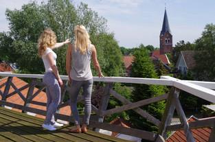 Zwei Frauen blicken von der Galerie auf den Kirchturm in Neermoor