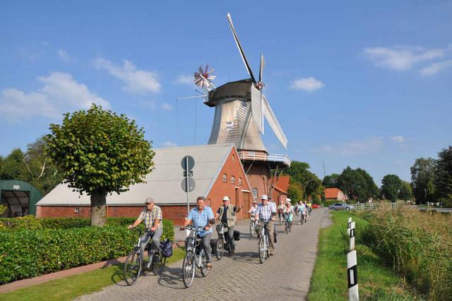Große Fahrradgruppe fährt an der Mühle in Warsingsfehn vorbei